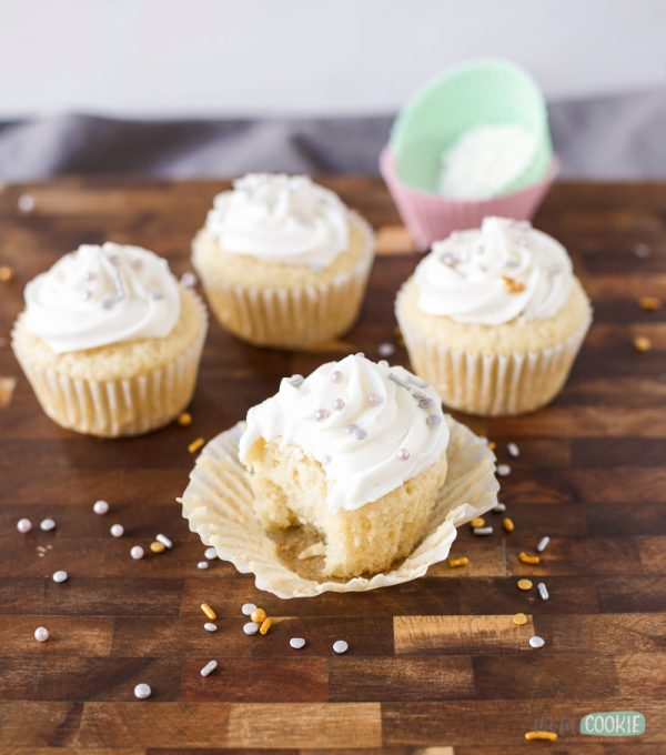 nut free vegan vanilla cupcakes on a wood board with a bite taken