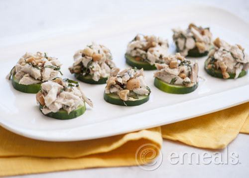white platter with Paleo Basil Cashew Chicken Salad on top of slices of cucumber