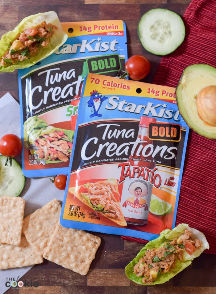 Spice up your lunchtime meals with these Spicy Tuna Lettuce Cups made with StarKist Tuna Creations BOLD Tapatío. These are gluten free, soy free, and nut free, so everyone can dig in! - #AD @TheFitCookie #TearEatGo | Tuna and vegetable salad in lettuce cups with avocado and crackers
