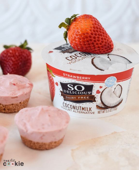 vegan mini strawberry cheesecakes next to container of So Delicious strawberry coconutmilk yogurt