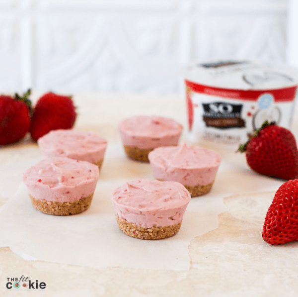 gluten free vegan strawberry cheesecakes arranged by strawberries near a container of So Delicious coconutmilk yogurt