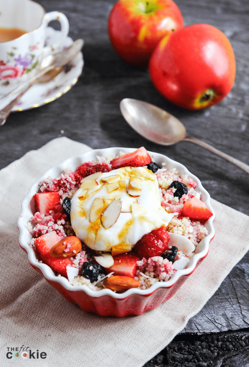 sweet mixed berry breakfast couscous topped with dairy free yogurt, almonds, and honey