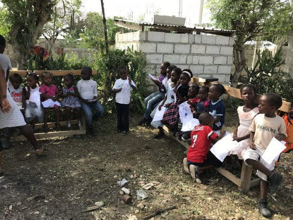 2 benches of Haitian students outside school ready to do a coloring project
