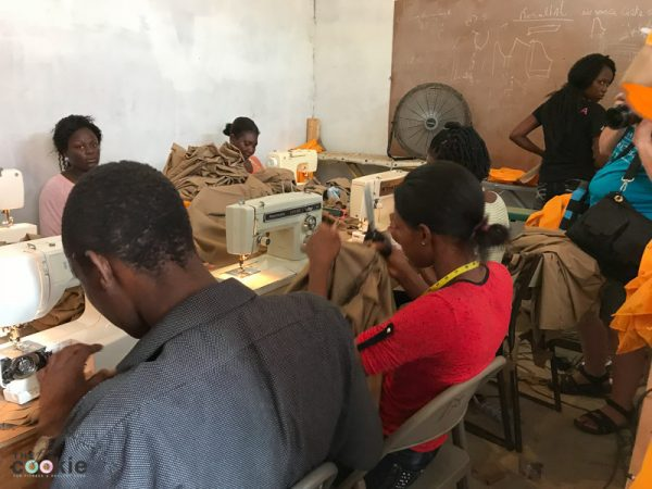Haitian parents sewing school uniforms for work