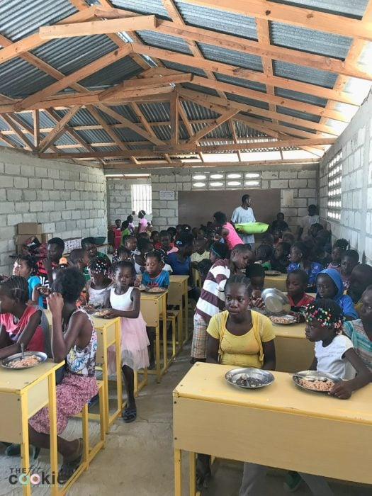 older Haitian students at Te Nwa school in their classroom eating lunch and waiting for their school photos