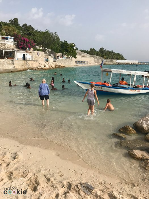 family in the water at the beach near a boat at Wahoo Bay resort in Haiti