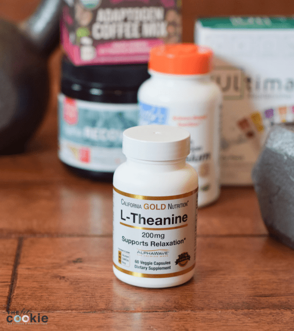bottle of L-theanine on a wood floor in front of other fitness supplements