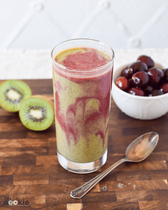 tall glass filled with green and pink dairy free cherry kiwi smoothie