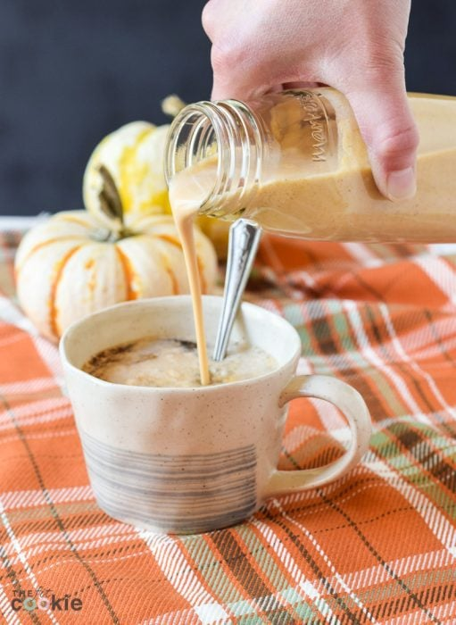 healthy sugar free pumpkin spice creamer being poured from bottle into cup of coffee