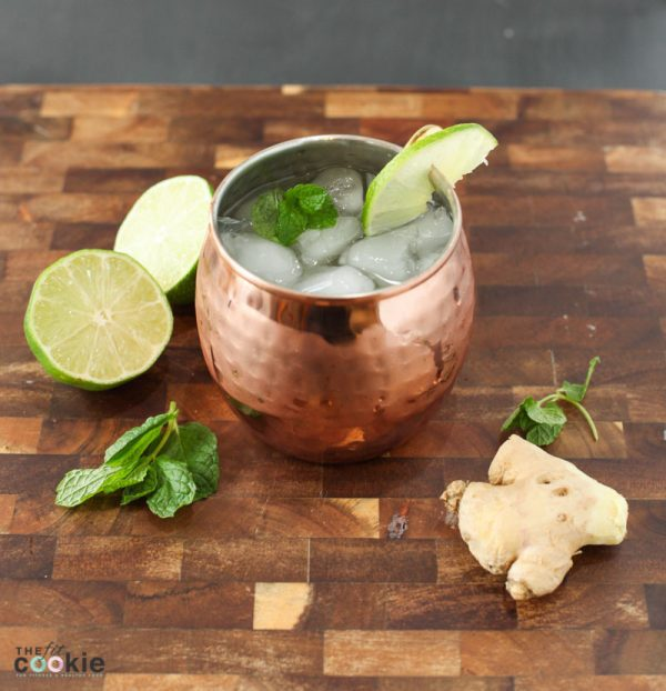 lower sugar moscow mule in a copper mug surrounded by fresh ginger, lime, and mint sprigs