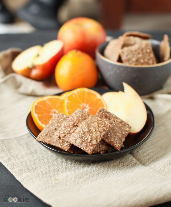 gluten free vegan cinnamon sugar crackers on a black plate with fruit slices
