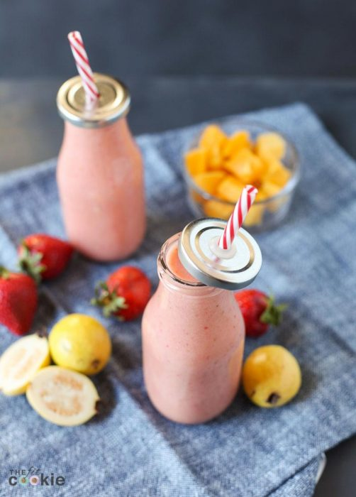 overhead photo of vegan strawberry guava smoothie in glass milk bottles