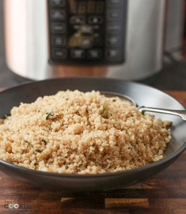 photo of instant pot quinoa in a black bowl in front of a pressure cooker