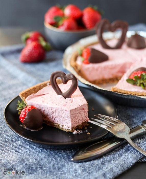 slice of strawberry vegan cheesecake on a black plate topped with a chocolate heart