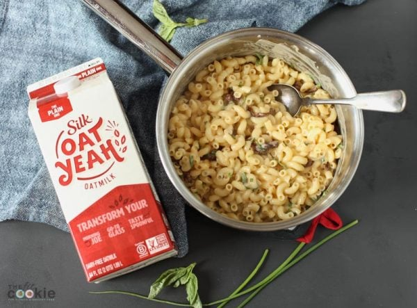 saucepan of sun dried tomato vegan dairy free mac next to a carton of Silk Oat Yeah oatmilk