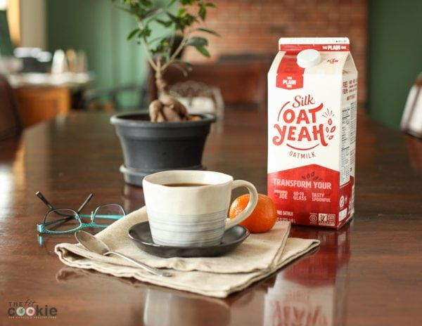 silk oat yeah carton on a table with a cup of coffee and an orange