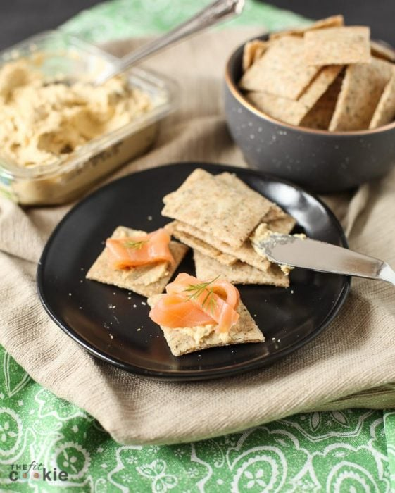 gluten free herb crackers on a lack plate, topped with smoked salmon