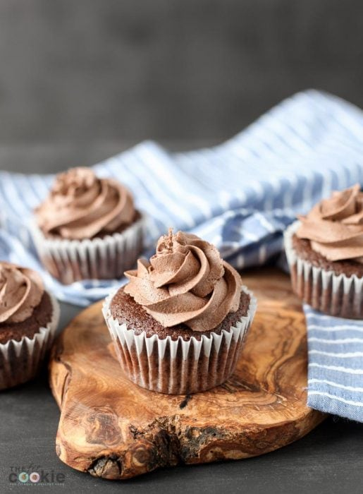 vegan chocolate cupcakes topped with chocolate buttercream in front of a blue napkin