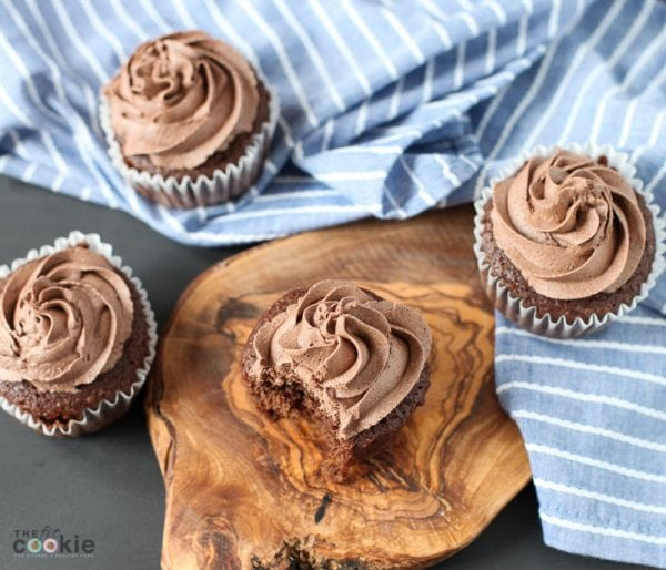 overhead shot of chocolate cupcakes with bite taken, on top of a wood board
