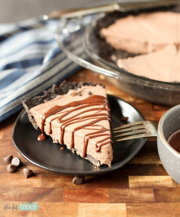 slice of dairy free chocolate cheesecake with chocolate drizzle on top on a black plate