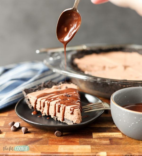 chocolate cheesecake slice with chocolate ganache being drizzled on top