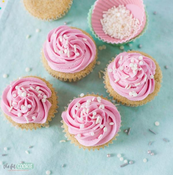 overhead photo of vegan vanilla cupcakes with star tip pink frosting decoration with white pearl sprinkles