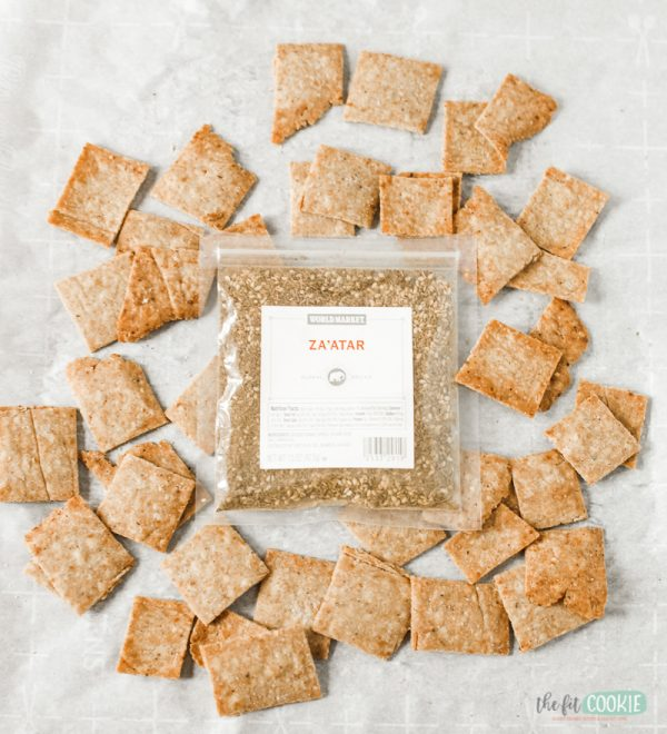 packet of za'atar seasoning next to gluten free za'atar crackers on parchment paper