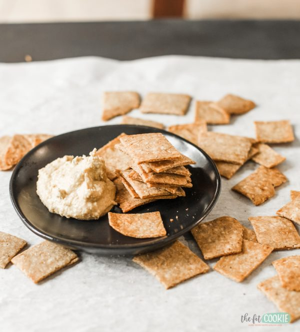 gluten free za'atar crackers on a black plate with hummus