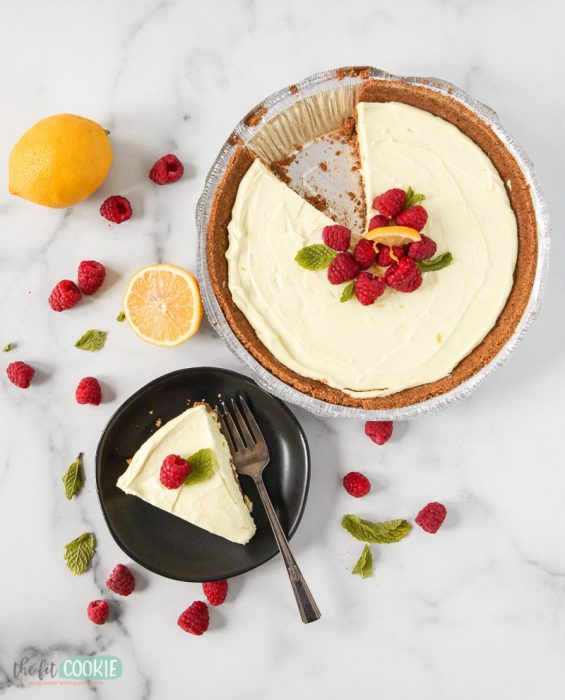 overhead photo of gluten free lemon cheesecake on a plate next to a pan of cheesecake