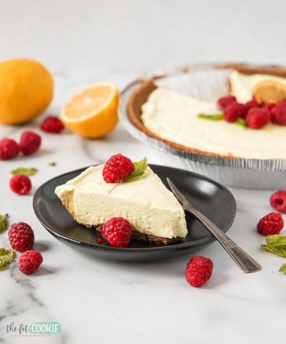 pretty slice of lemon cheesecake on a black plate with a fork