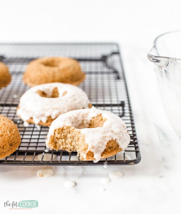 top 8 allergen free carrot cake donuts on a cooling rack with vegan cream cheese donut glaze
