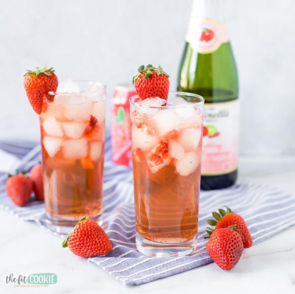glass of sparkling grapefruit mocktail next to strawberries