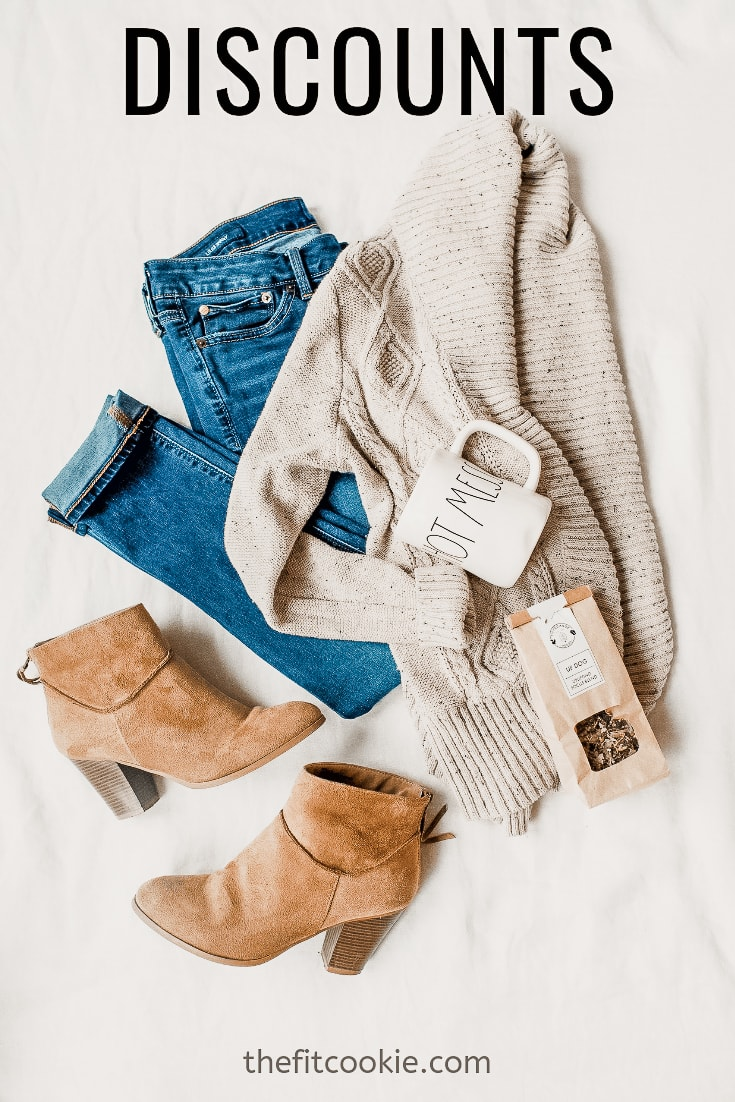 flat lay photo of sweater, mug, jeans, and boots on a blanket
