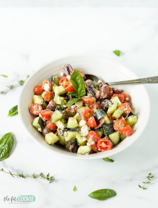 gluten free greek salad in a white bowl topped with basil leaves