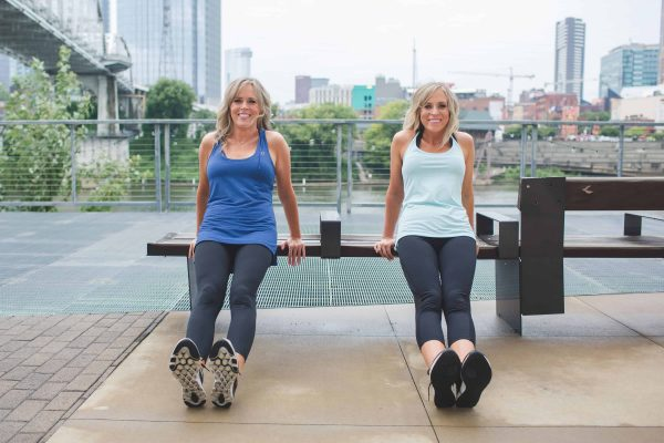 2 women doing dips off a bench outside - hotel room workout