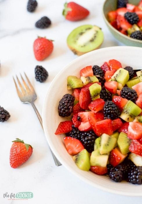 paleo blackberry kiwi fruit salad in a white bowl on a marble surface