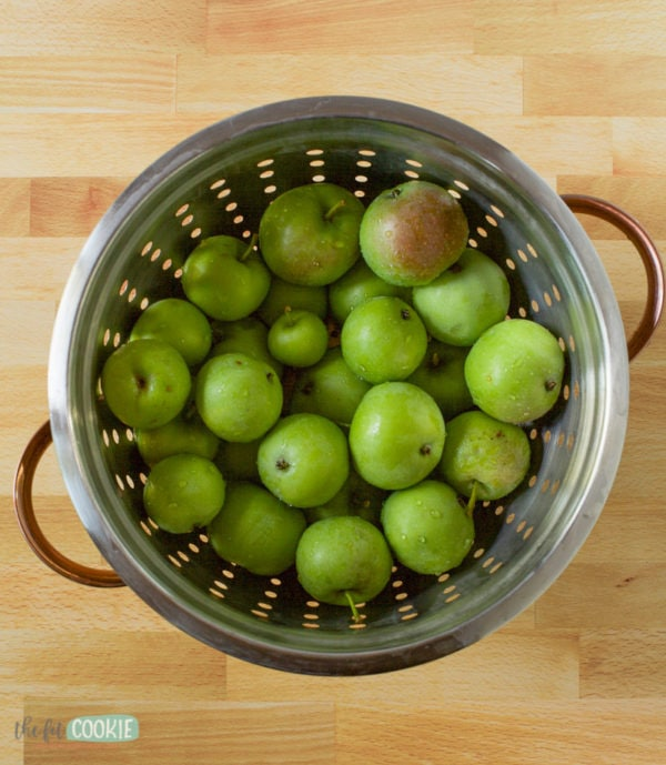 overhead photo of colander filled with small green apples