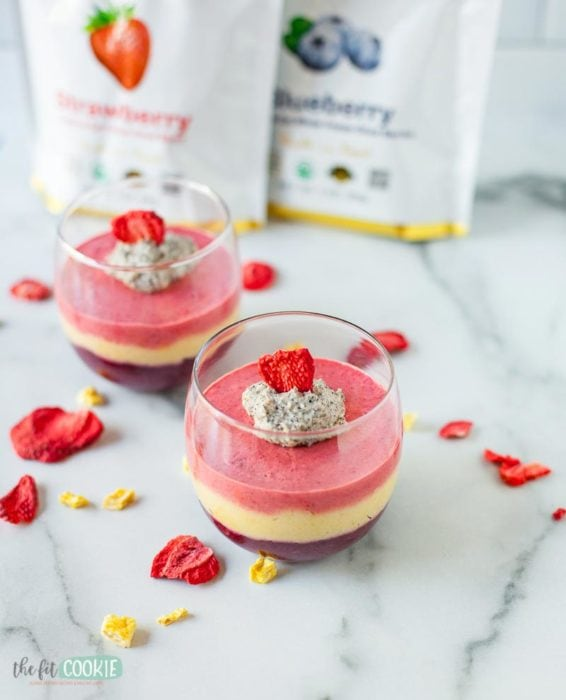 layered fruit mousse in a glass with freeze dried strawberry slice as garnish