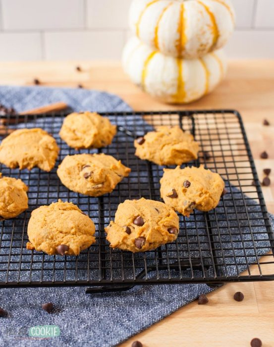 vegan pumpkin chocolate chip cookies on a black cooling rack