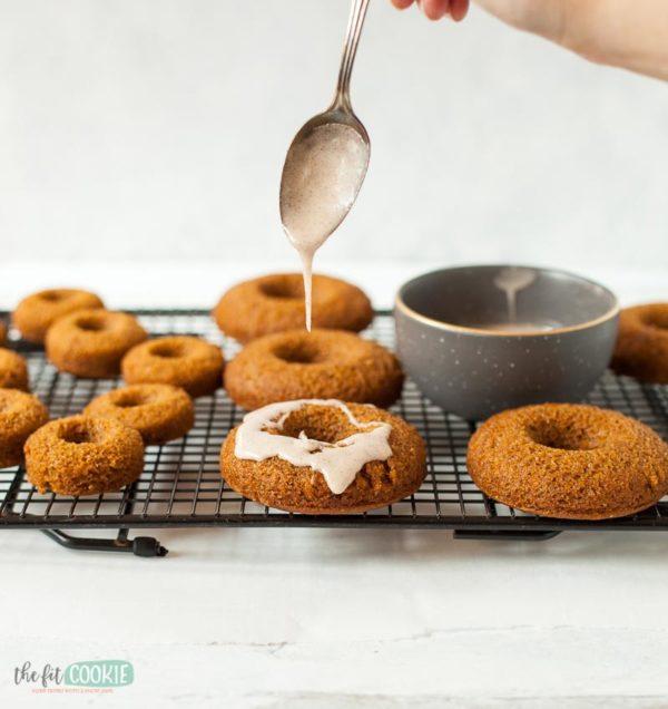 adding cinnamon glaze to a batch of pumpkin baked donuts