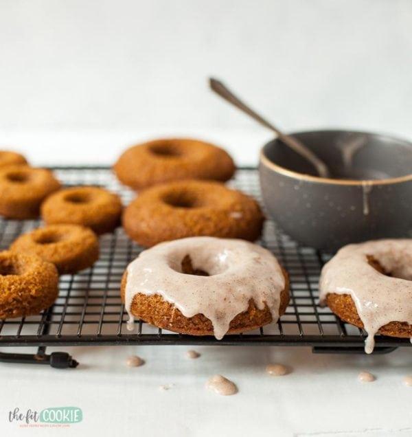 pumpkin spice donuts on a wire rack with cinnamon glaze