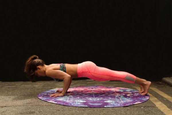 woman doing chaturanga on a yoga mat