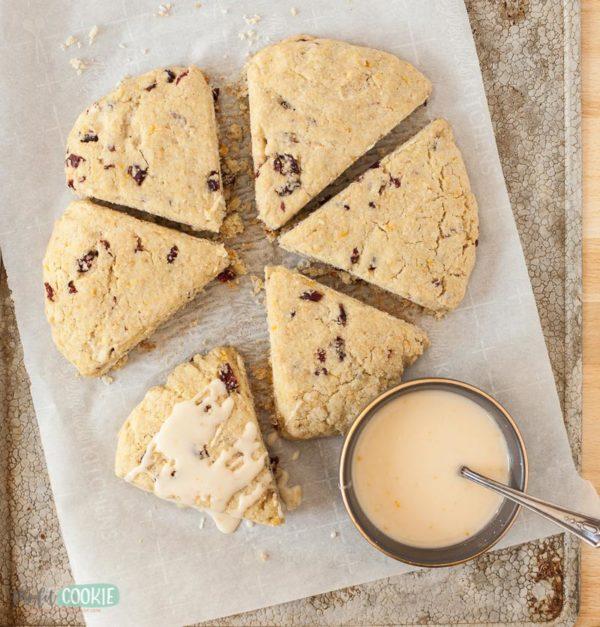 vegan cranberry scones on a baking sheet with orange glaze