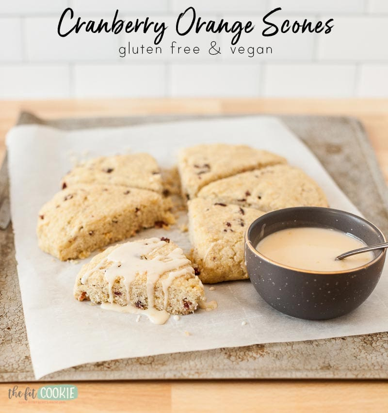 photo of gluten free cranberry orange scones on a baking sheet with orange glaze drizzled on top