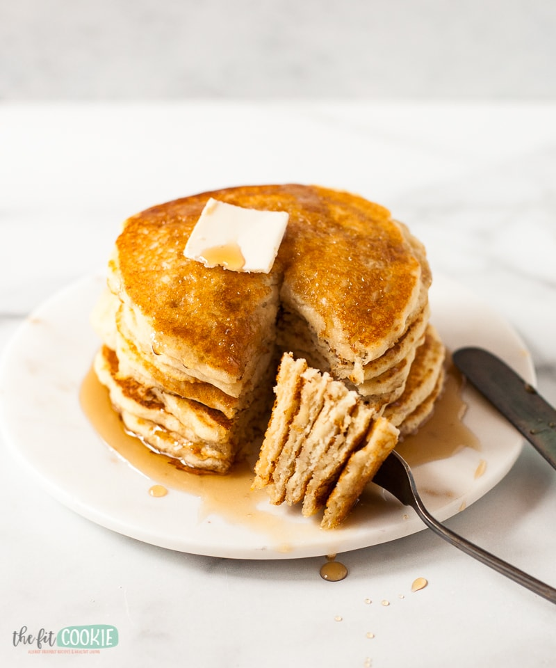 stack of buttermilk pancakes with slices on a fork