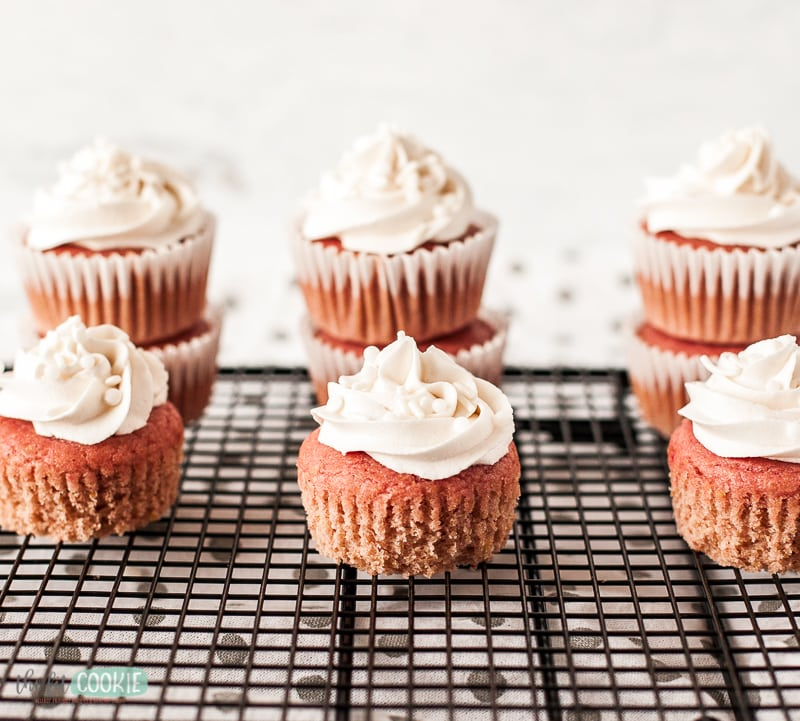 strawberry cupcakes with white frosting on cooling rack