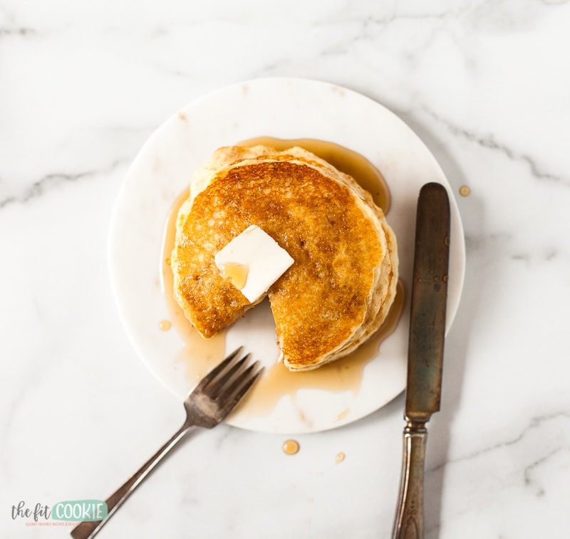 overhead photo of pancakes with butter and syrup on them