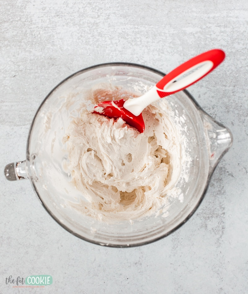 frosting in a glass bowl with a red spatula