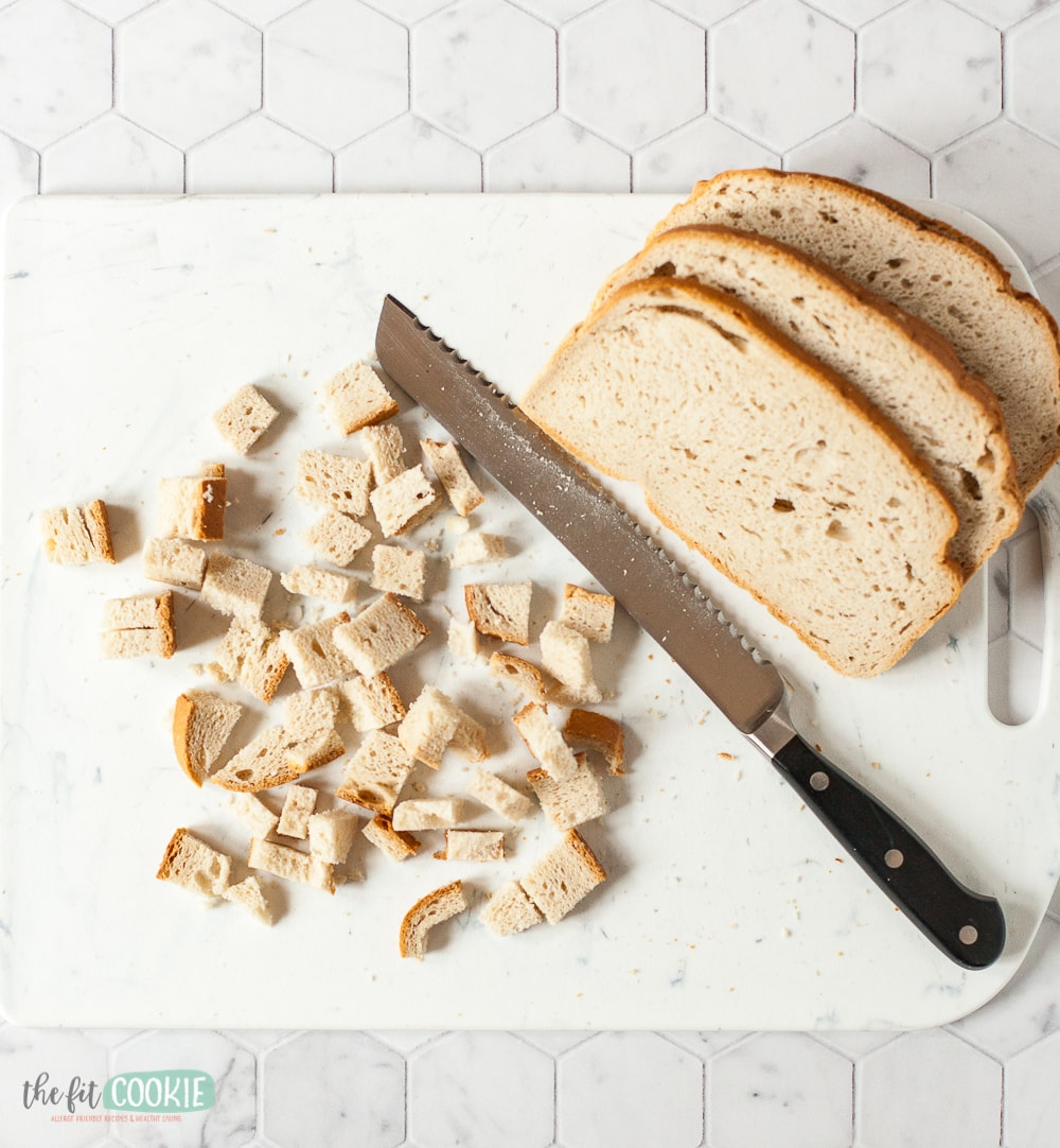 cubes of bread and a knife on a cutting board