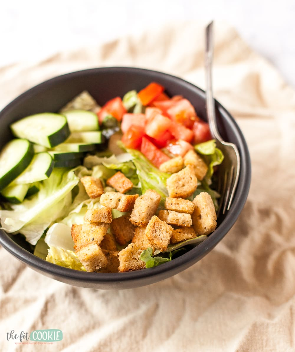 salad with croutons in a black bowl